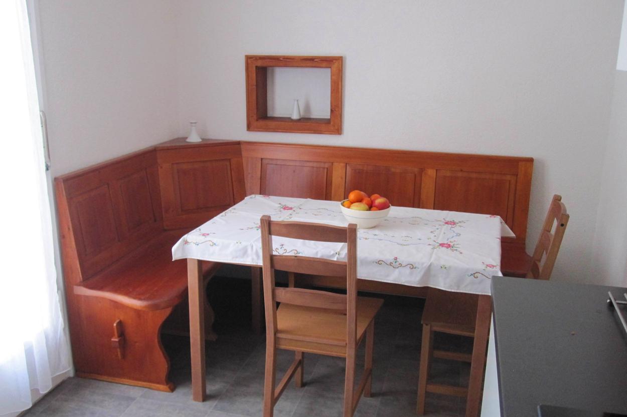Gemütlicher Esstisch mit Eckbank und Durchreiche ins Wohnzimmer