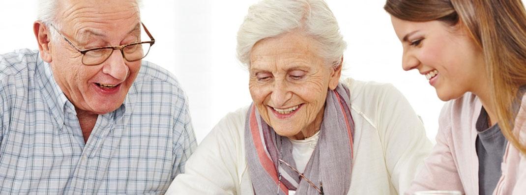 Pflegerin des mobilen Pflegedienstes Karlsruhe im Gespräch mit einem Seniorenehepaar.