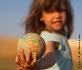 Mädchen unscharf hält Globus in der Hand nach vorne.