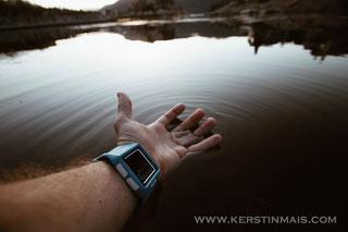 Arm mit Uhr über einem See.