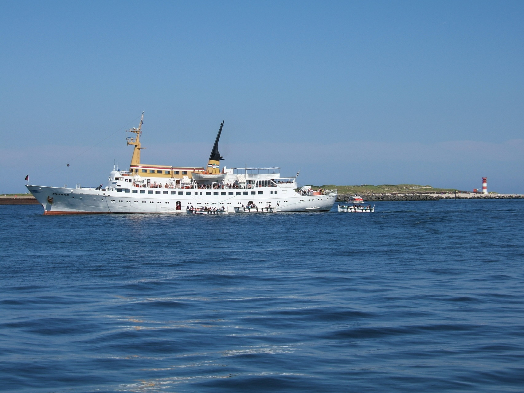 Die MS Atlantis auf Reede vor Helgoland und der Badedüne