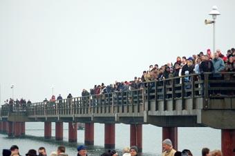 Schaulustige auf der Seebrücke für das traditionelle Anbaden an der Seebrücke
