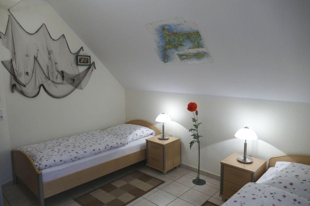 Schlafzimmer mit 2 Einzelbetten, Mückengittern, verstellbaren Lattenrosten, Verdunkelungsrollos und TV.