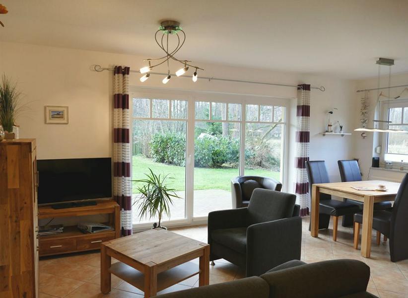 Der Wohnraum mit Sofa, Essecke und Zugang zur Terrasse / zum Garten