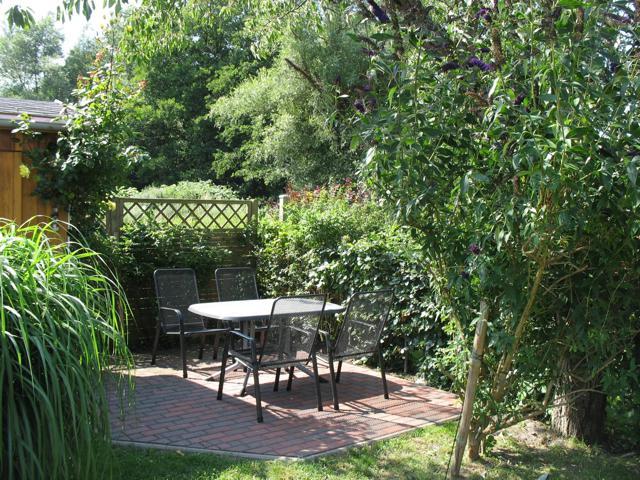 Die Außenterrasse der Ferienwohnung Haiderose mit Grillhütte und Gartenmöbeln