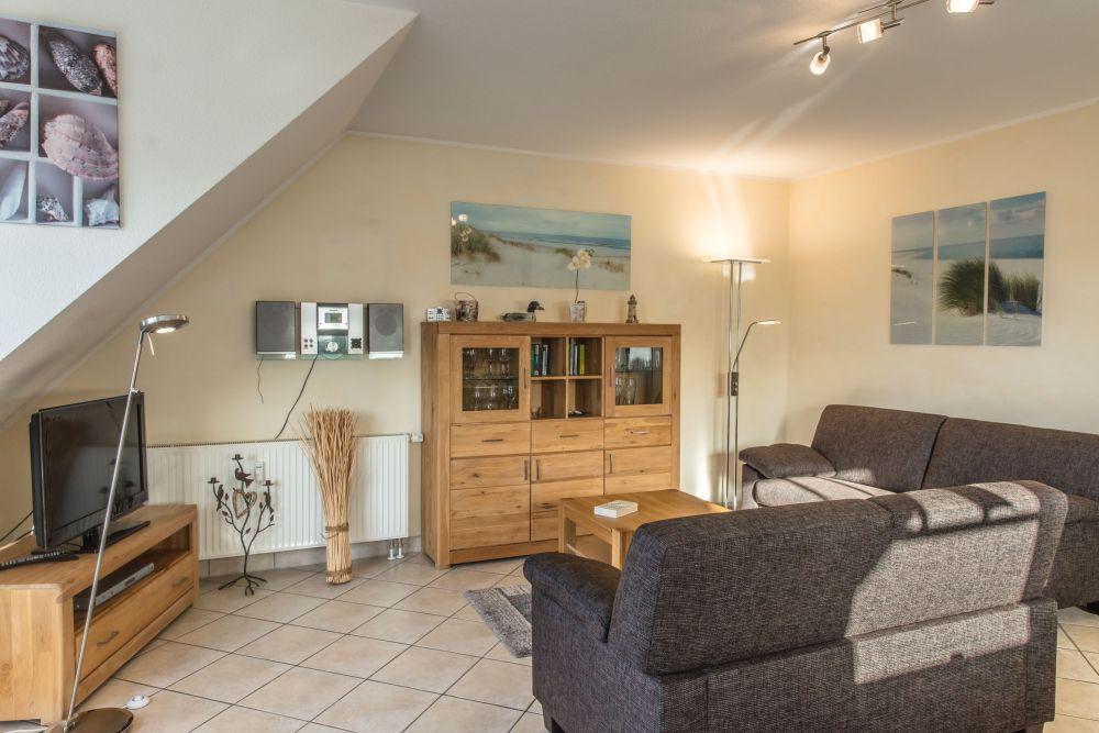 Wohnzimmer der Ferienwohnung mit hochwertigem Sofa, Flachbild-TV und HiFi-Anlage.