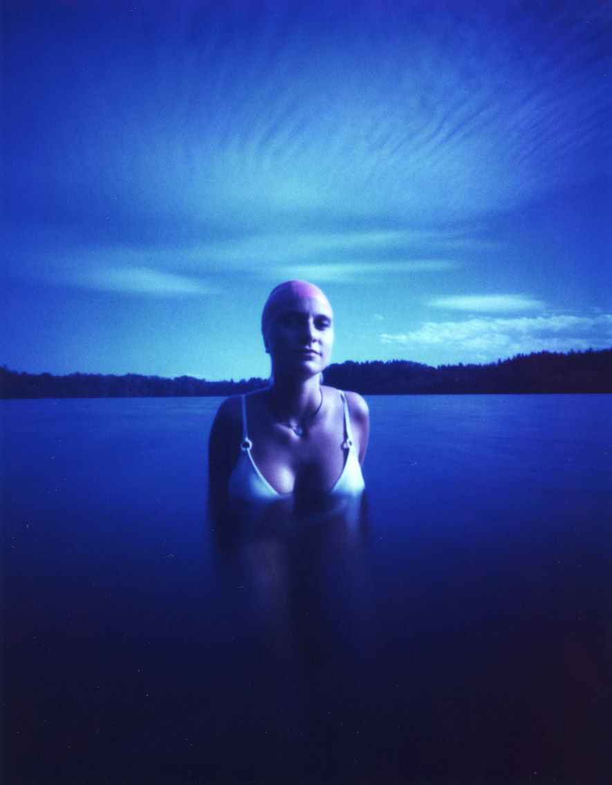 Junge Frau mit einer Camera Obscura auf Polroidfilm im See aufgenommen als Farbphoto