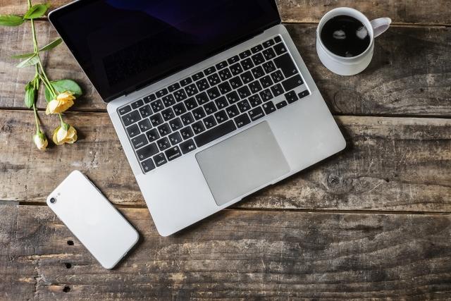 デスクの様子。ノートパソコン、観葉植物、手帳とペン。コーヒーカップに手が添えられている。