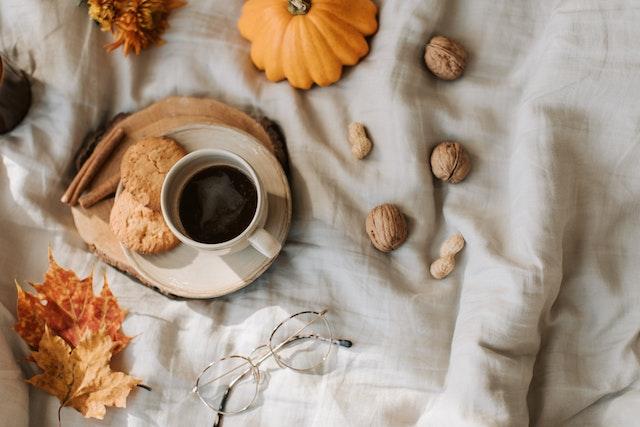 ノートパソコンを広げながらミーティング中の女性社員。テイクアウトのコーヒー。