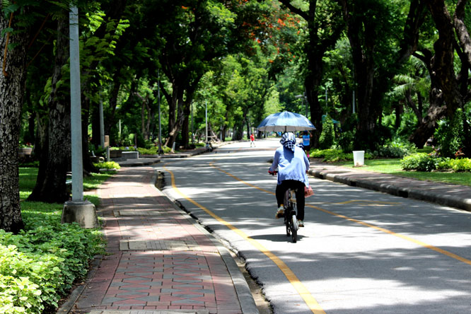 Woman on bike riding in a park in Bangkok