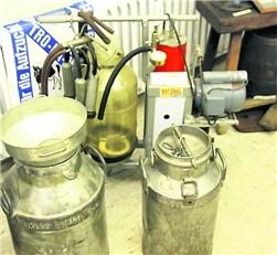 Landwirtschaft früher: Milchkannen und dahinter eine Melkmaschine aus den 50er Jahren.