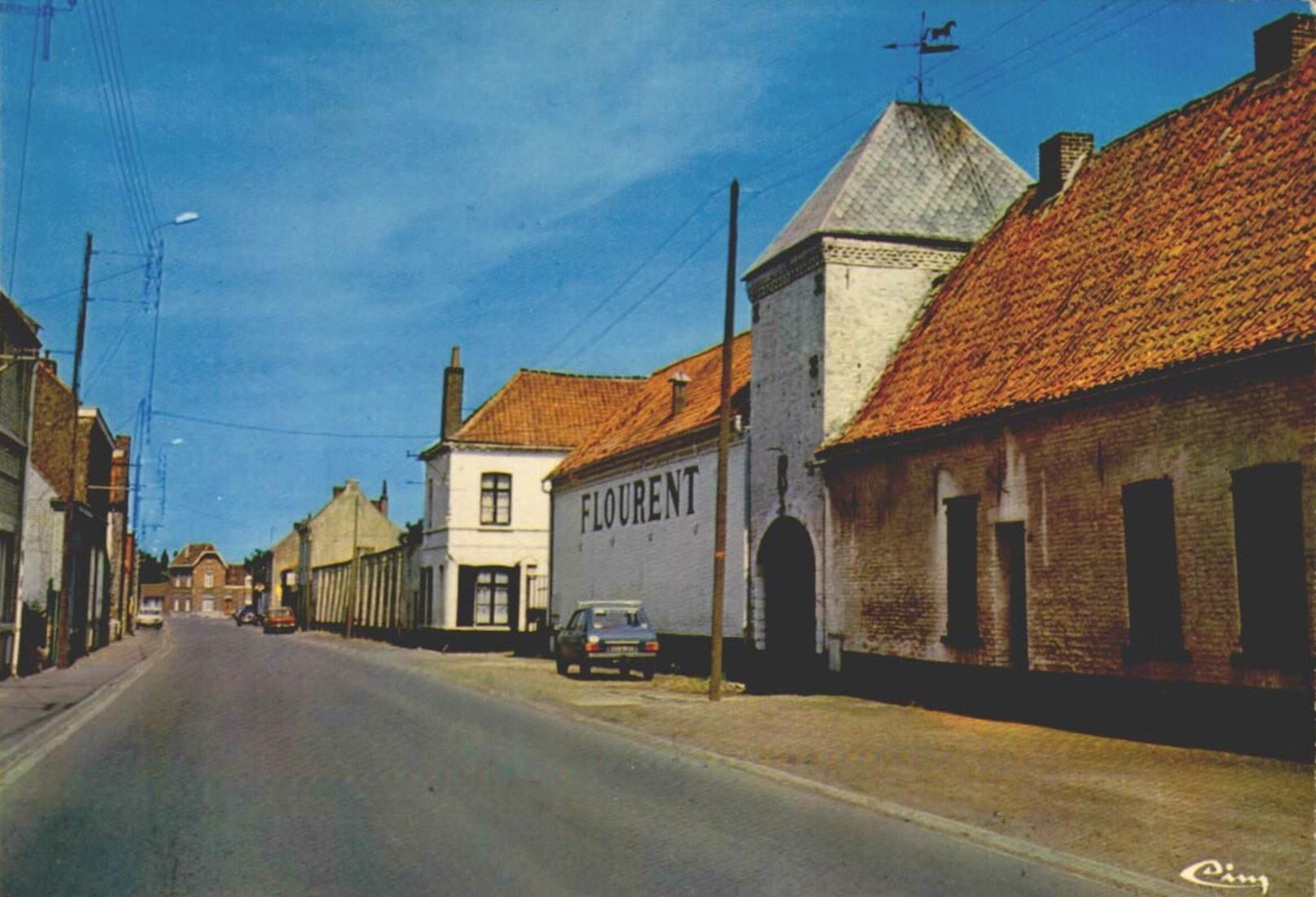 """Carte postale vue depuis la rue Sonneville où se situait la distillerie. On y voit le porche de 1779 de l'ancienne """"cense de Layens"""""""