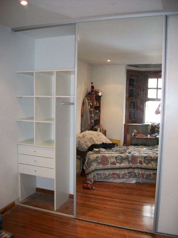 Interior de placard. De Pared a pared blanco con puertas 2 en melamina y 1 espejo