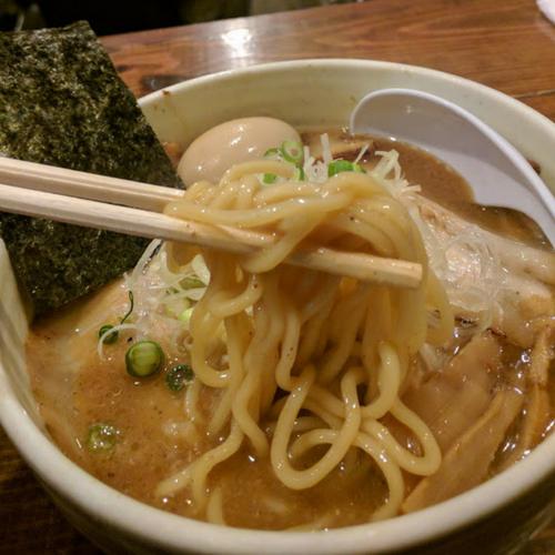 味玉チャーシュー麺を割り箸で食べるところ