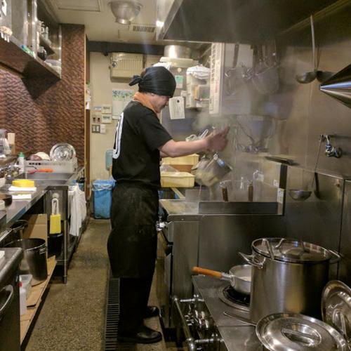 厨房で麺の湯切りをする佐藤さん