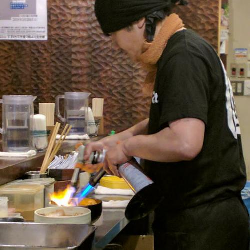 カウンター越しに厨房でチャーシューを炙る様子が見える