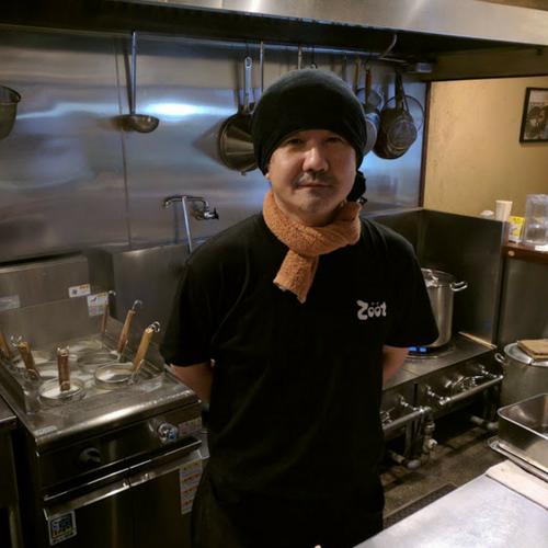 らーめんZoot店主佐藤さん 厨房で黒いTシャツ、黒いタオルを頭にまいている