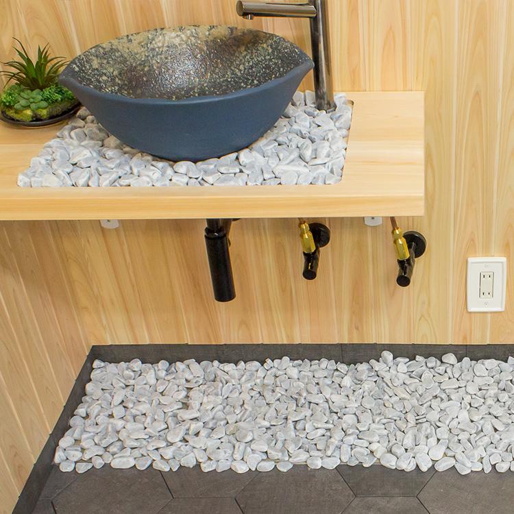 ▲洗面所の手洗ボウル下と床に玉砂利を敷いた事例