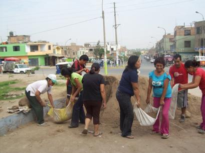 Parents d'élèves transportant avec les moyens du bord de la terre arable pour le biojardin aux 12 fonctions du collège Suecia de Año Nuevo (Lima - Pérou)