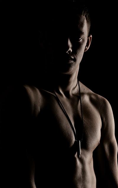 Low-Key-Aufnahme eines muskulösen, jungen Mannes mit freiem Oberkörper