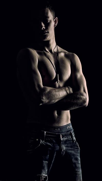Lowkey eines jungen Mannes mit freiem Oberkörper in Jeans vor schwarzem Hintergrund
