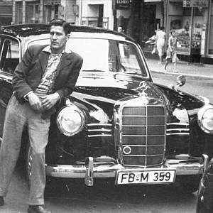 "Oskar Mallmann, Elvis Taxifahrer in der Kurstraße Bad Nauheim. Im Hintergrund u.a. ""Leder Wedel"""