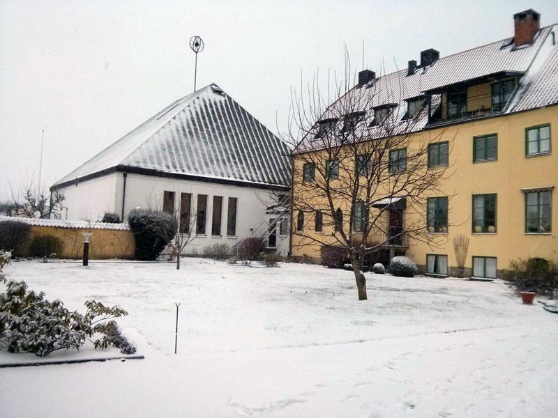 Kirche und Gästehaus im Schnee.