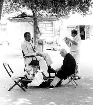Roma, Settembre 1974 - Bianco lustra scarpe a uomo di colore alla stazione Termini