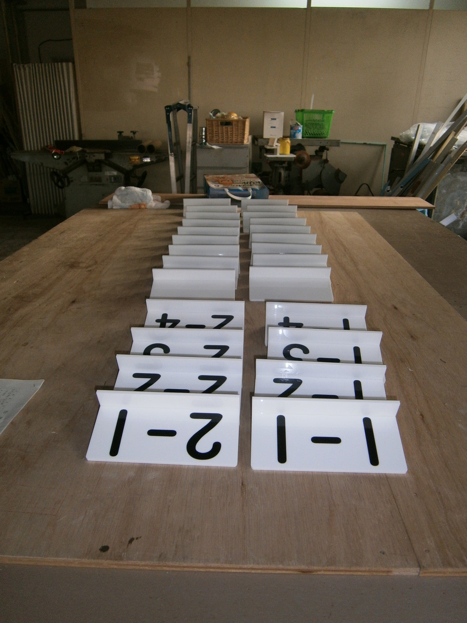 小学校の下駄箱上に設置するクラス名プレートです。L字に曲げたアクリルに切文字を貼っています。