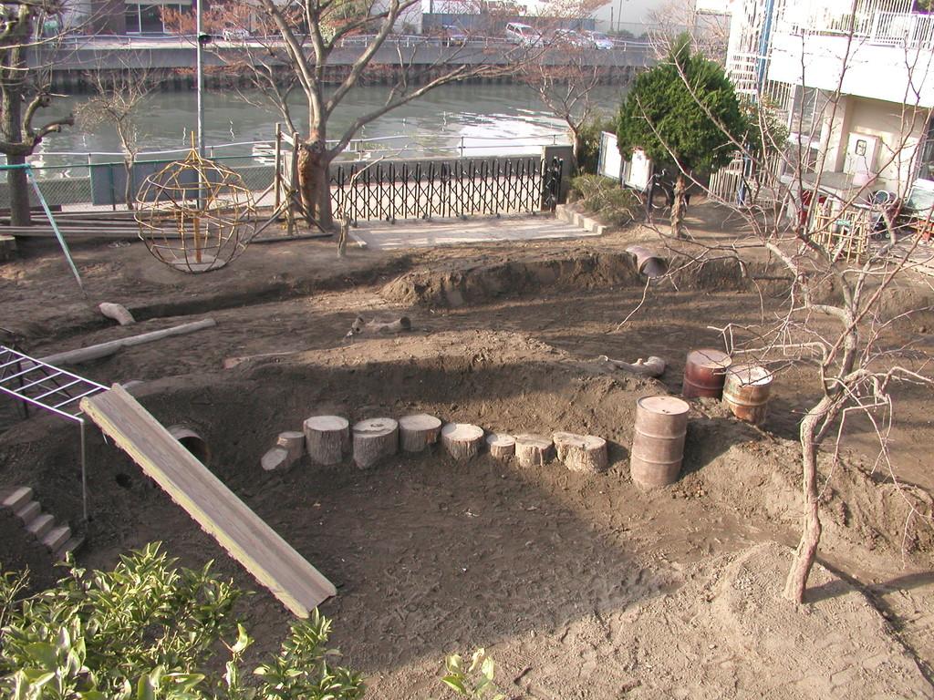 2003. 4. 1 撮影(その2)塹壕(ざんごう)だらけの園庭。どこに行くのも上がったり降りたりの繰り返し。足腰が徹底的に鍛えられます。この年臨時採用された四十代の保育士が一週間で「腰ががくがくになった。」と言って辞めてしまった。子供達の腰がそれに耐えていることが証明された珍事。