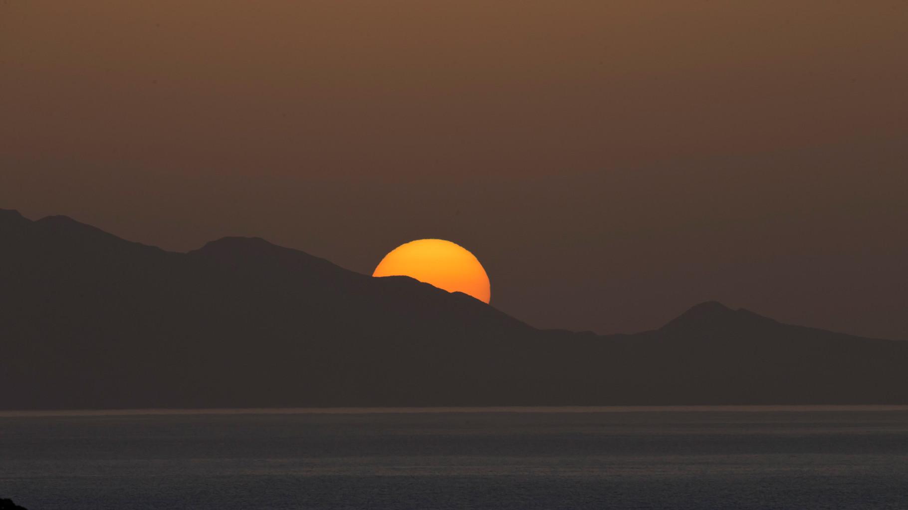 ... versinkt die Sonne langsam hinter einem Hügelzug am Meer.