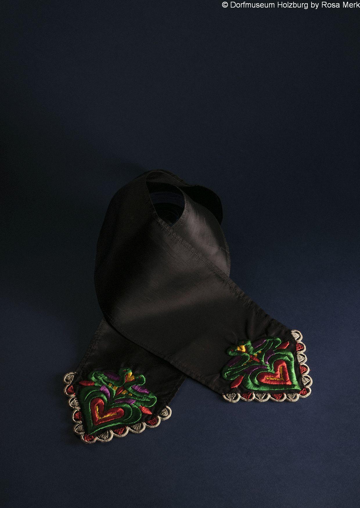 Krawatte für Schwälmer Männertracht, 20. Jh., schwarzes Moiréeband, Spitzen mit Herzen und Vögelchen bunt bestickt