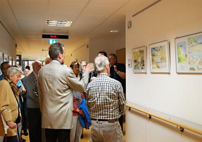 Der Künstler beschreibt den interessierten Gästen Motivation und Motive der ausgestellten Gemälde