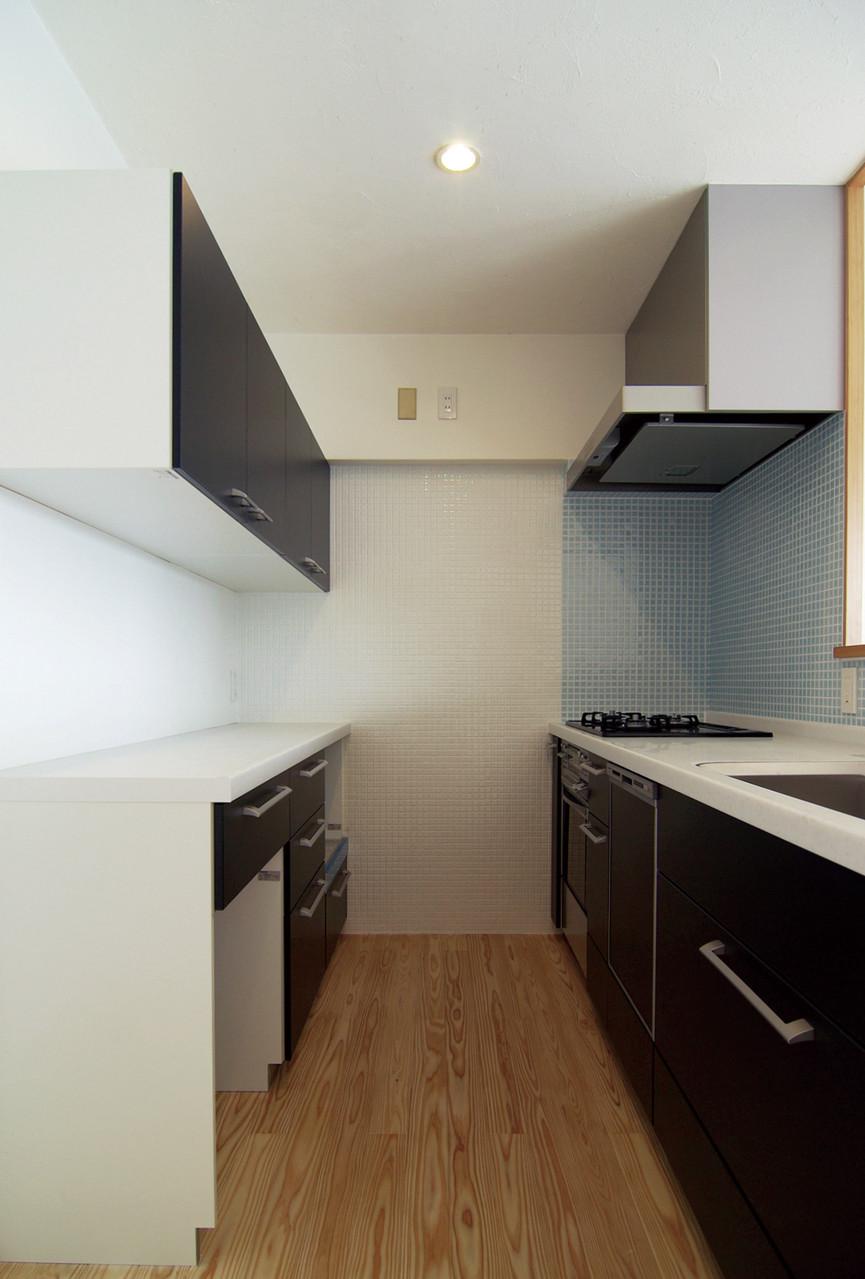 キッチン廻り壁は一部モザイクタイル仕上。左吊戸棚は通常より低く取付け出し入れがしやすいよう工夫。