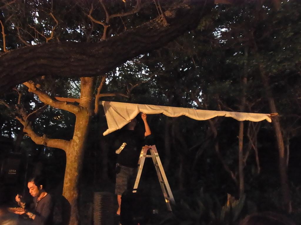 木の枝に渡したスクリーン。下では焼きそばを食べる人も。