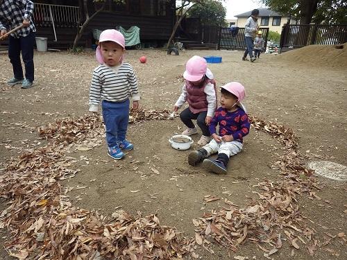 秋あそび「落ち葉で輪っかを作ったら自然と輪っかの中にはいるうさぎぐみ(1歳児)」
