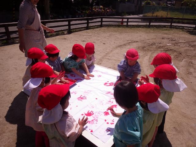 3歳児(かぜ組)はクラスカラーのあか色ともも色の絵の具で 手形あそびをしました。かわいい手の模様がいっぱいできました。