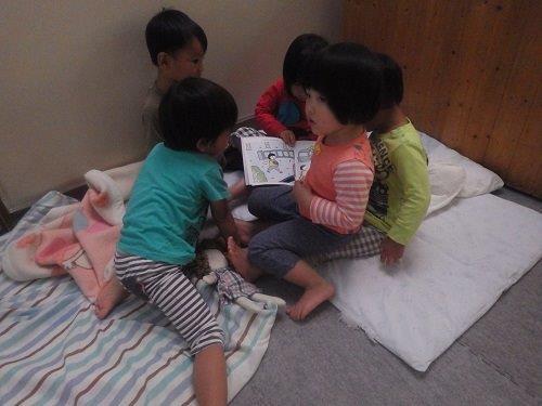 <2歳児>絵本が大好き子どもたち。よく大人のひざに座って絵本を楽しんでいます。まねっこしてお友だちをひざに乗せては、一緒に絵本タイムでほっこり。