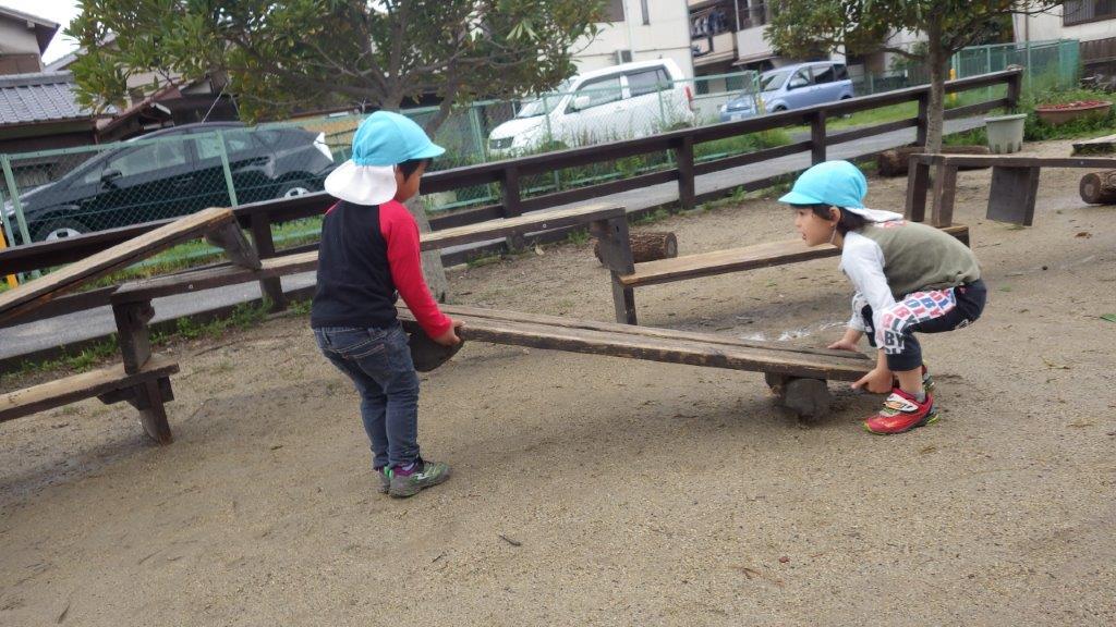 「戸外あそび」木のベンチを協力し合ってアスレチック作り。職員手作りのベンチはあそびの中で乗り物になったりおうちになったりテーブルになったりいろんなものに変身!子どもたちのあそびに欠かせないものになっていますよ。