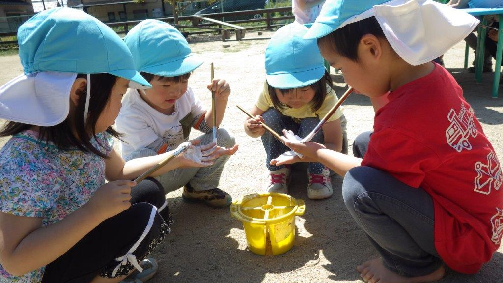 「手作りこいのぼり」白の絵の具を手に塗って布にぺたぺた。繰り返し楽しむ子どもたちでした。赤いこいのぼりはかぜぐみ(3歳児)、水色のこいのぼりはそらぐみ(4歳児)、緑のこいのぼりはやまぐみ(5歳児)です。青空の下で気持ちよさそうに泳いでいましたよ。