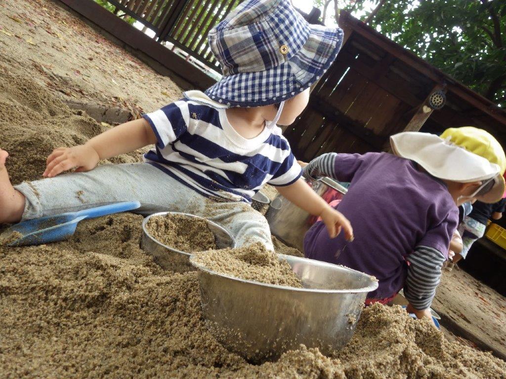 砂をにぎにぎ感触をめいっぱい楽しんでいます。