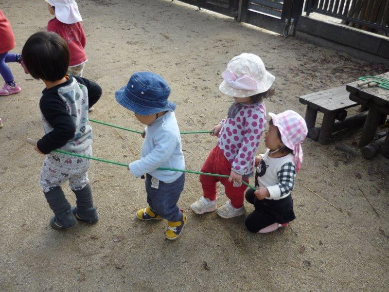 電車ごっこでひよこぐみ(0歳児)をのせて車掌さん気分のつきぐみ(2歳児)。