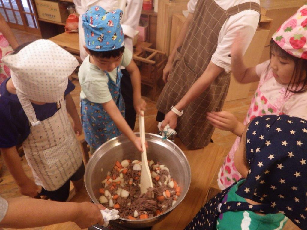 「宿泊保育」自分たちで育てた人参、玉ねぎ、じゃがいも、にんにく、小麦粉を使ってカレーライス作り。切って大きな鍋で炒めておいしくな~れ♪と楽しそうに作る子どもたち。育てたミニトマトときゅうりはサラダに、ナスは浅漬けにしました。
