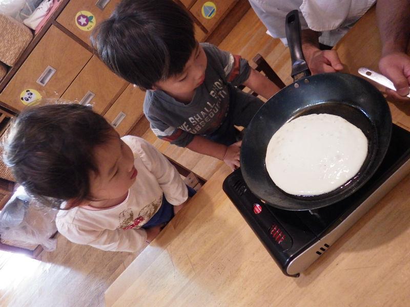 【2歳児(つき組)】大きいカステラがたべたい!絵本「ぐりとぐら」にでてくるカステラのようなホットケーキをクッキングしました。卵と小麦粉と牛乳を混ぜて、目の前で焼いてもらってやけていく様子をみていた子どもたち。大きなお口でかぶりついていまいた。
