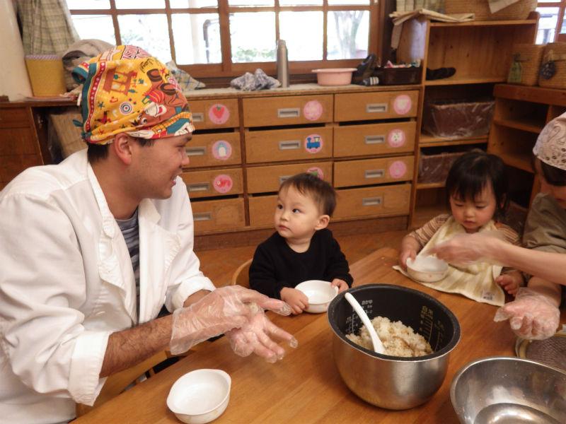 【1歳児(うさぎ組)】おやつの時間、調理さんに目の前でおにぎりをにぎってもらったうさぎぐみさん。興味津々でみつめてはおいしそうに食べていました。