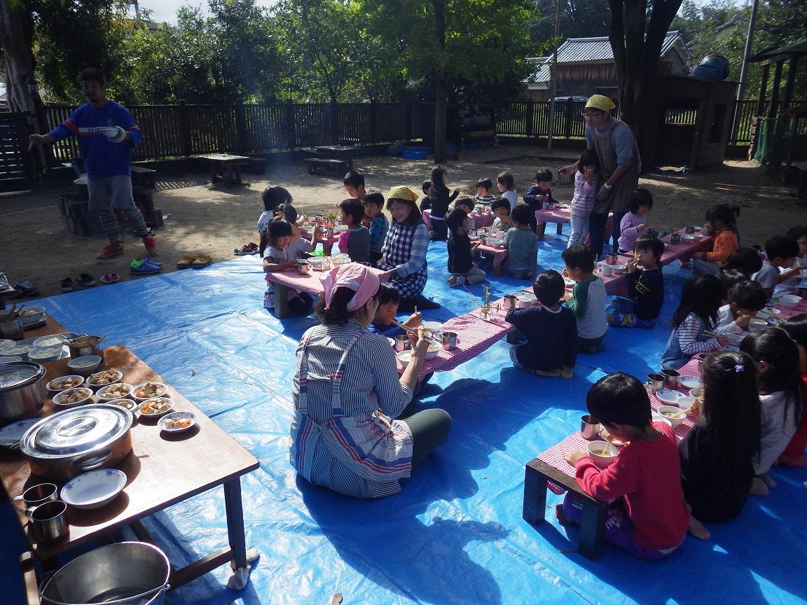 「収穫祭」秋の恵みに感謝して、園で育てて収穫したさつま芋や里芋をいれてやま・そら(4・5歳児) はエプロンをつけてクッキングをしました。園庭にかまどを作って秋空の下、みんなでおいしくいただきました。