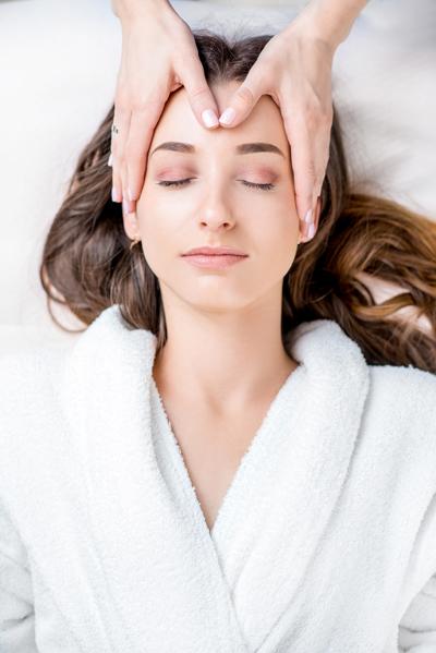 Frau mit geschlossenen Augen bekommt Anti Stress Behandlung