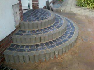 Exklusive Pflasterarbeiten sind ein Blickfang für jeden Eingangsbereich, wie hier bei diesem dreistufigen runden Tritt.