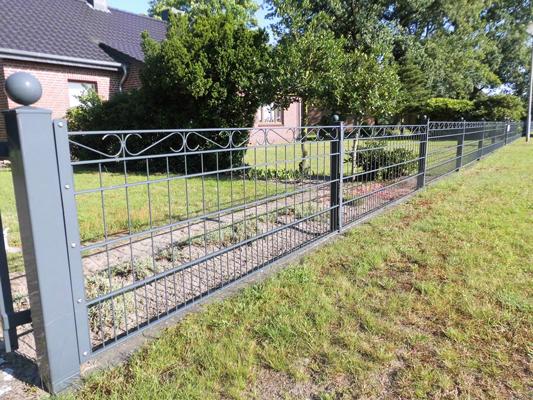 Ein kunstvoll aber modern verzierter Zaun rund um ein Privatgrundstück.