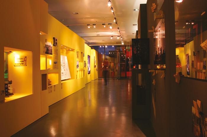 Die gelbe Wand mit Vitrinen für Exponate